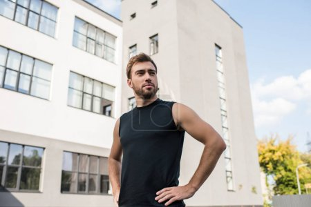 Photo for Young man in sportswear posing with hands on waist outside - Royalty Free Image