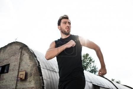 Athletic man jogging outside