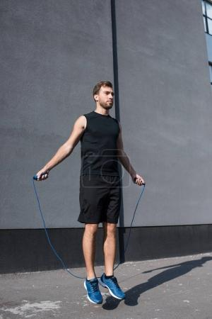 athletic sportsman jumping with rope