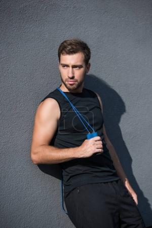 Photo pour Jeune homme athlétique, posant avec corde à sauter sur son épaule - image libre de droit