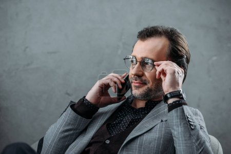 Photo for Stylish middle aged businessman in eyeglasses talking on smartphone and looking away - Royalty Free Image