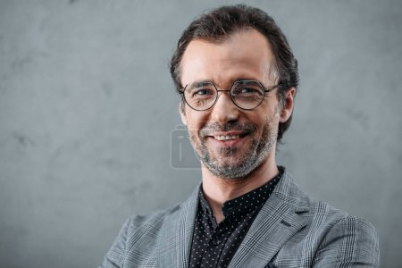 Photo for Handsome stylish middle aged businessman in eyeglasses smiling at camera - Royalty Free Image
