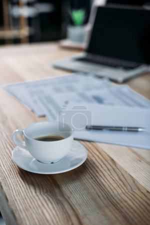 cup of coffee and laptop on table