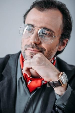 Photo for Close-up portrait of handsome businessman in eyeglasses holding hand on chin and looking away - Royalty Free Image