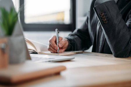 businessman taking notes in notebook