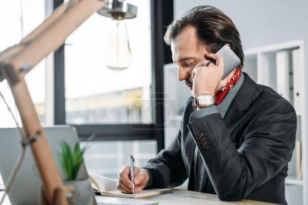 Photo pour Homme d'affaires parler sur smartphone et prendre des notes au bureau - image libre de droit