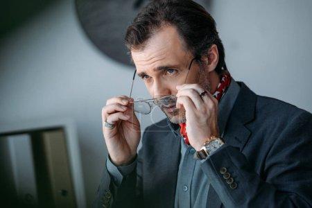 businessman holding eyeglasses