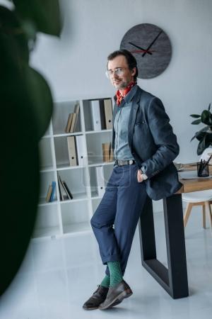 Foto de Guapo hombre de negocios elegante en anteojos de pie con las manos en los bolsillos y sonriendo a cámara - Imagen libre de derechos