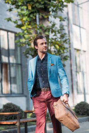 Photo for Handsome stylish middle aged man holding leather bag and looking away outside - Royalty Free Image