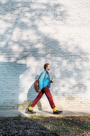 Photo for Side view of stylish man with shoulder bag drinking coffee to go on street - Royalty Free Image