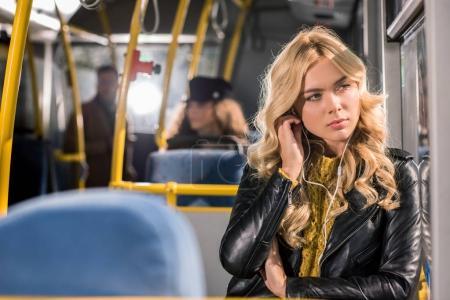 Photo pour Jeune fille blonde songeuse écouteurs en regardant la fenêtre dans le bus - image libre de droit