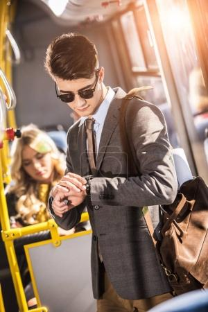 businessman checking wristwatch in bus