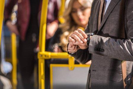 businessman checking wristwatch in bus