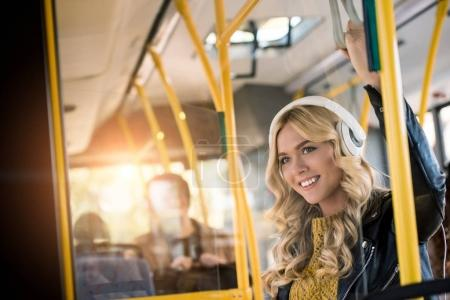 Photo for Beautiful happy young woman in headphones listening music in bus - Royalty Free Image