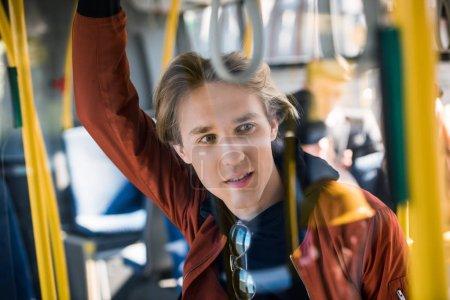 Photo pour Beau jeune homme à la recherche de suite en se tenant debout dans le bus - image libre de droit