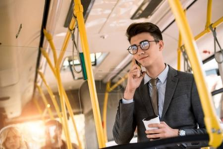 Photo for Smiling young businessman in eyeglasses talking on smartphone and drinking coffee in bus - Royalty Free Image