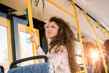 Photo for Low angle view of smiling young woman in eyeglasses standing in public transport - Royalty Free Image