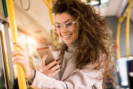 Photo pour Bonne humeur jeune femme à l'aide de smartphone en se tenant debout dans les transports publics - image libre de droit
