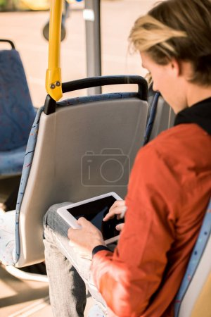 man with digital tablet in bus
