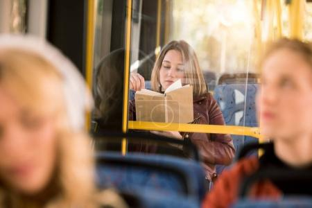 girl reading book in bus