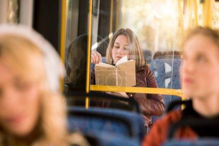 Photo pour Mise au point sélective de livre de lecture de jeune femme en bus de la ville - image libre de droit
