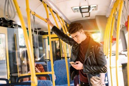 Photo pour Beau jeune homme en veste de cuir à l'aide de smartphone dans le bus - image libre de droit