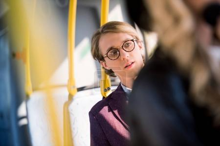 young man in eyeglasses in bus