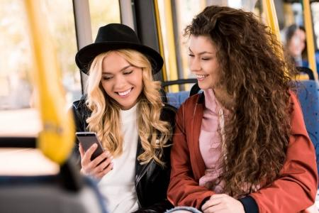 girls using smartphone in bus
