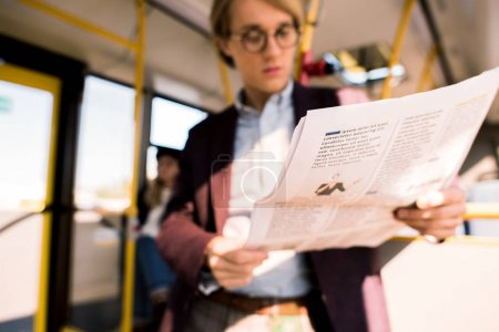 Photo for Close-up view of young businessman in eyeglasses reading newspaper in bus - Royalty Free Image