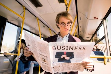 Photo for Handsome young businessman in eyeglasses reading newspaper in bus - Royalty Free Image