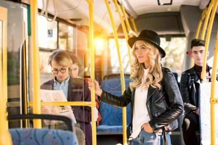 Photo pour Belle fille blonde souriante en veste de cuir et chapeau permanent et en regardant loin en bus - image libre de droit