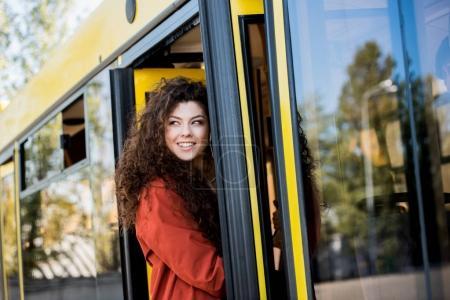 Photo pour Beau sourire bus entrée jeune femme et vous cherchez loin - image libre de droit