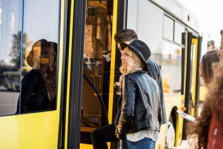 Photo for Smiling young couple holding hands and entering city bus - Royalty Free Image