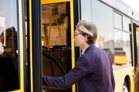 young man entering bus