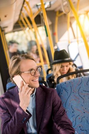 man using smartphone in bus