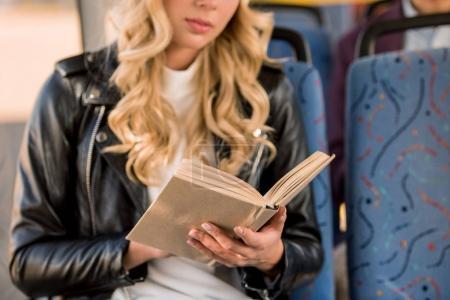 Photo pour Recadrée tir de fille blonde en blouson de cuir, lecture de livre dans le bus - image libre de droit