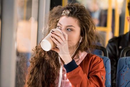Photo pour Belle jeune femme buvant du café de tasse de papier en bus de la ville - image libre de droit