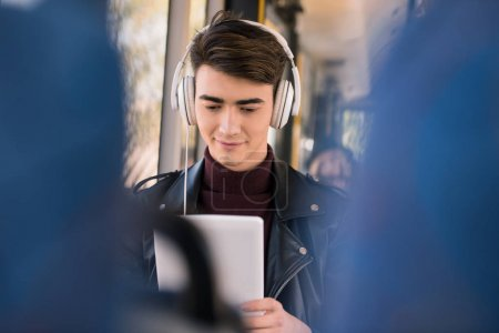 man in headphones with digital tablet