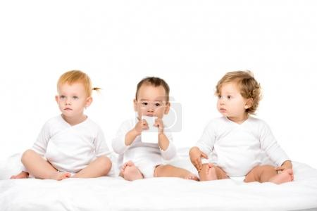 Photo for Multicultural  toddlers with smartphone sitting in row isolated on white - Royalty Free Image