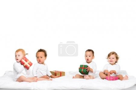 Photo for Cute multiethnic toddlers holding wrapped gifts isolated on white - Royalty Free Image