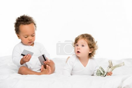 Photo for Multiethnic toddlers holding money and credit cards isolated on white - Royalty Free Image
