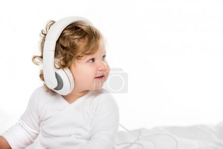 Photo for Portrait of smiling toddler listening music in headphones isolated on white - Royalty Free Image