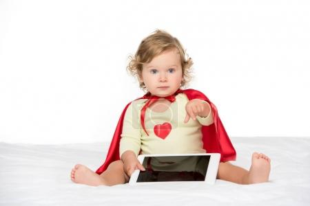 toddler in superhero cape with tablet