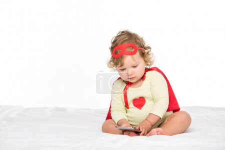 toddler in superhero costume with smartphone