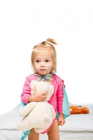 Photo pour Portrait de jeune fille en cape de super-héros tenant ours en peluche isolé sur blanc - image libre de droit