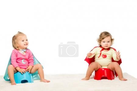 Photo for Adorable toddlers in superhero capes sitting on potties isolated on white - Royalty Free Image