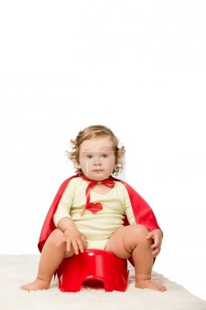 toddler in superhero cape with pottie