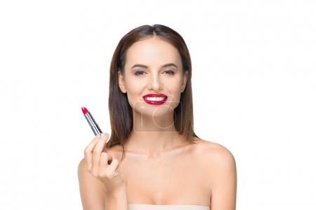 Photo pour Belle jeune femme nue tenant rouge à lèvres et souriant à la caméra isolé sur blanc - image libre de droit