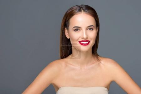 Foto de Retrato de mujer joven atractiva sonriendo a cámara aislada en gris - Imagen libre de derechos