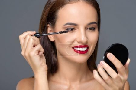 Photo pour Femme jeune joyeuse, appliquer le mascara avec pinceau isolé sur fond gris - image libre de droit